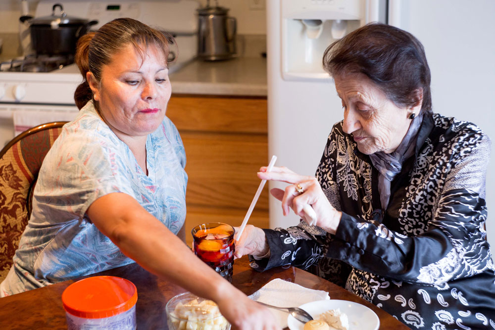A Home Health Aide assisting an elderly woman with a meal